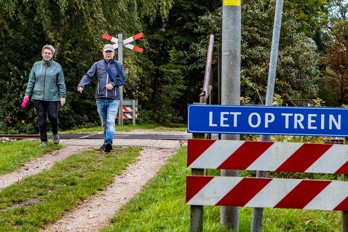 """Sylvia Dorenbosch en Dirk Wolff, twee van de vele wandelaars in Diepenveen, zien de noodzaak niet van afsluiten of andere maatregelen bij de overgang. ,,Er gebeurt hier nooit iets."""""""