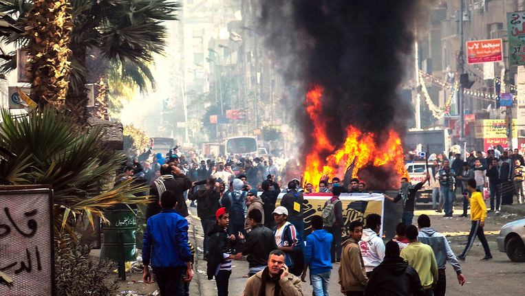 Egyptische demonstranten steken een politieauto in brand tijdens de anti-coup-protesten in Gizeh vandaag Beeld getty