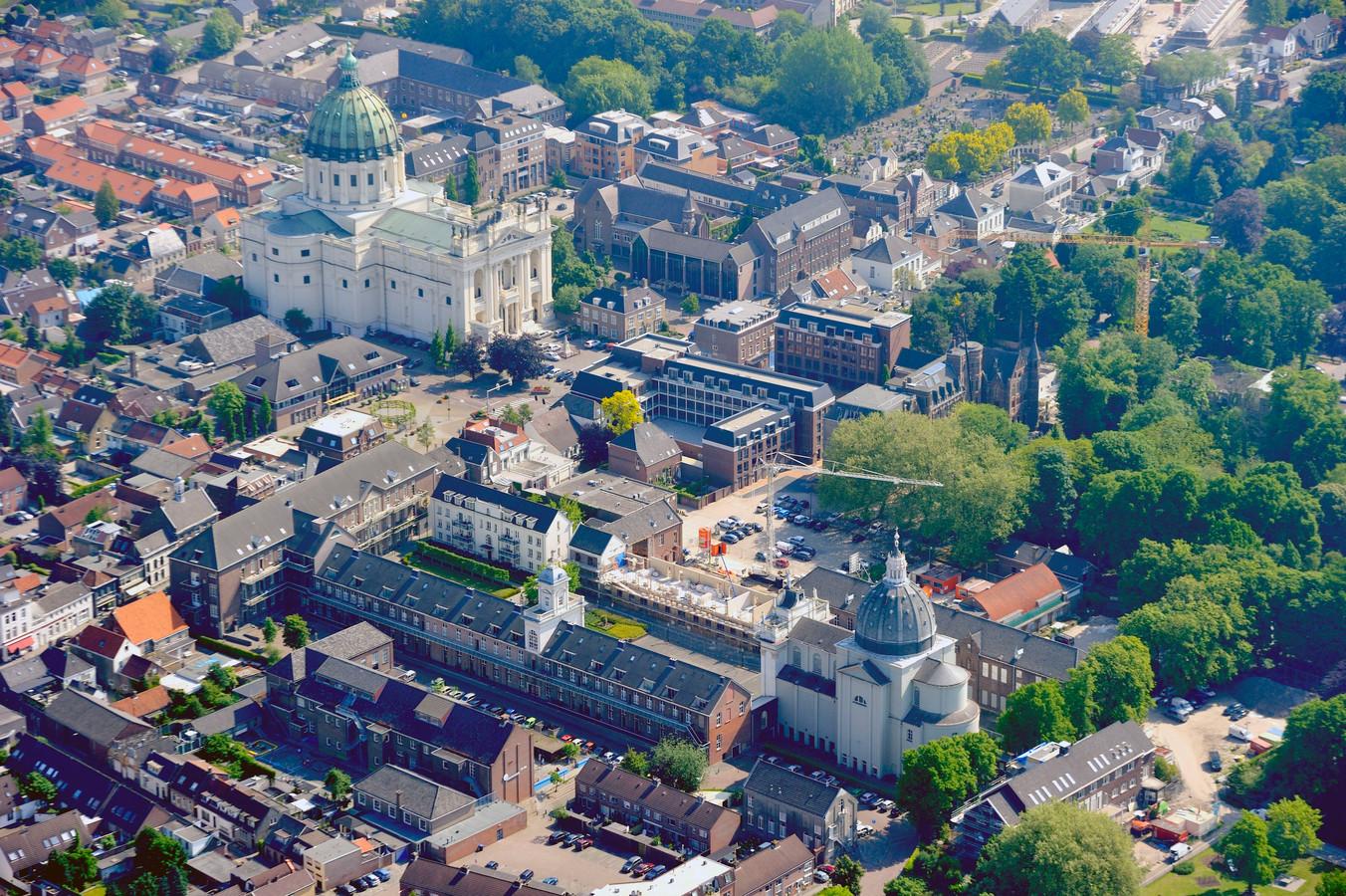 Luchtfoto van Oudenbosch. Rechts van de basiliek Sint Anna met daarachter de muziekschool, die tegen de vlakte gaat. Vooraan de kapel van Saint Louis met rechts de Mariabouw. Daar komt het cultuurcluster.