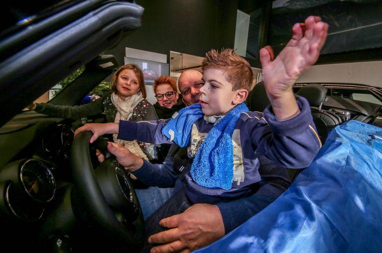 Maxim aan het stuur van een Mini met zijn zus en ouders.