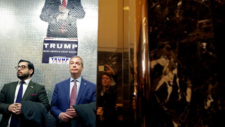 Nigel Farage (in blauw pak) staat in de lift in Trump Tower. Beeld Getty Images