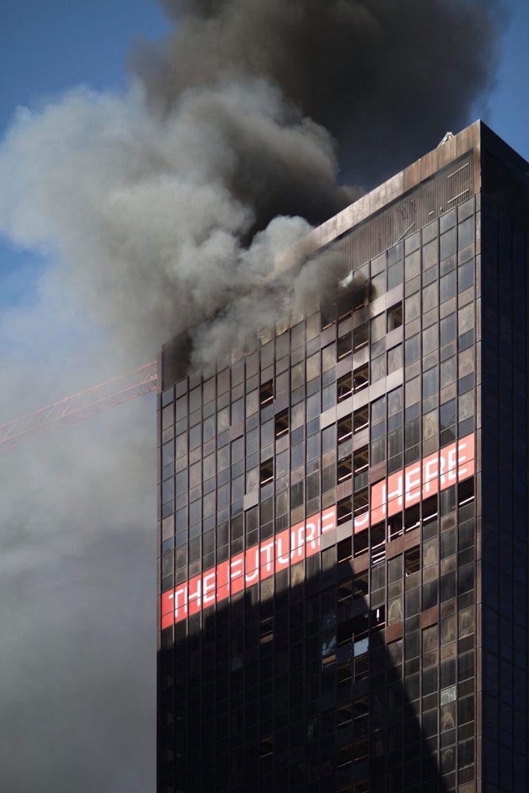 Uit het gebouw stijgt een dikke rookwolk op.