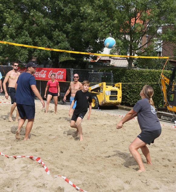 De beachvolleyballers profiteren van de zon tussen twee plensbuien door.