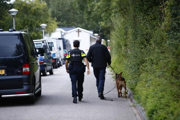 Agenten doen met speurhonden onderzoek bij het woonwagenkamp in Zwolle.