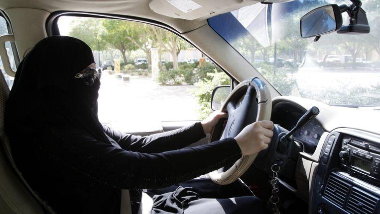 Een Saoudische vrouw protesteert tegen het rijverbod door achter het stuur te kruipen. Beeld epa