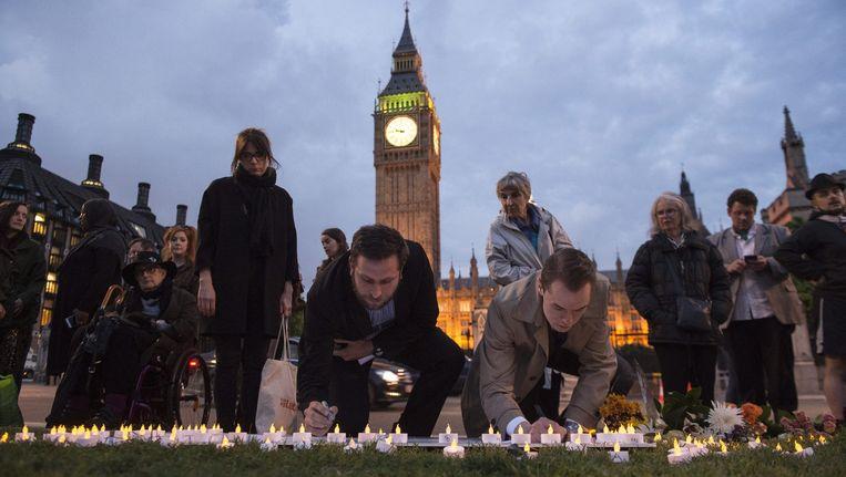 Britten steken kaarsjes aan om Jo Cox de laatste eer te bewijzen. Op de achtergrond is de Westminster Abbey te zien. Beeld Reuters