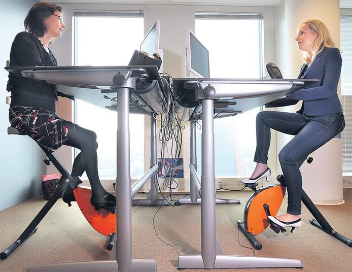 Ambtenaren van VWS op hun 'deskbike'.
