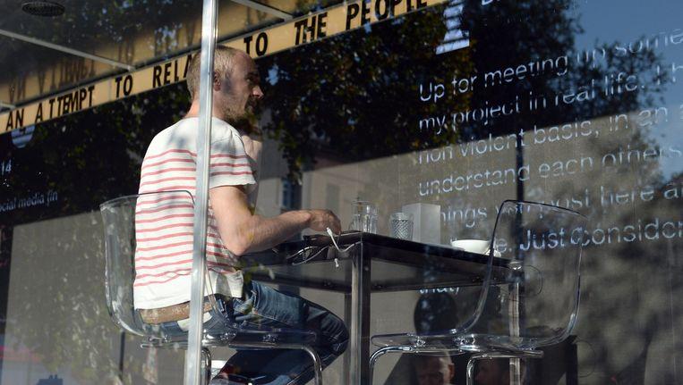 Kunstenaar Dries Verhoeven zit in een glazen container in Berlijn (4 oktober 2014). Tijdens deze openbare voorstelling worden de chatgesprekken die hij voert via datingsites op een scherm getoond. Beeld ANP
