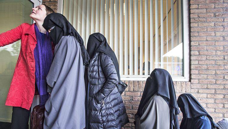 Advocaten, familieleden en sympathisanten van de verdachten uit Den Haag wachten bij rechtszaal in Amsterdam-Osdorp, bekend als de bunker, om te worden binnengelaten voor het jihadproces. De Haagse rechtbank is voor de veiligheid uitgeweken naar Osdorp. Beeld Foto Guus Dubbelman / de Volkskrant