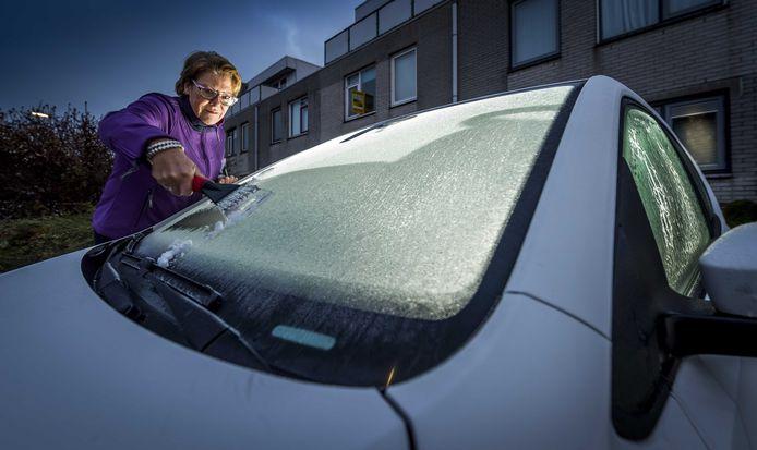 Een vrouw krabt de ruiten van een auto.