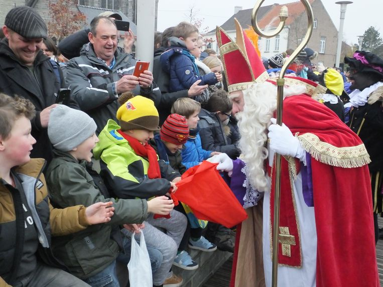Sinterklaas kijkt of deze jongen al genoeg snoep gekregen heeft.