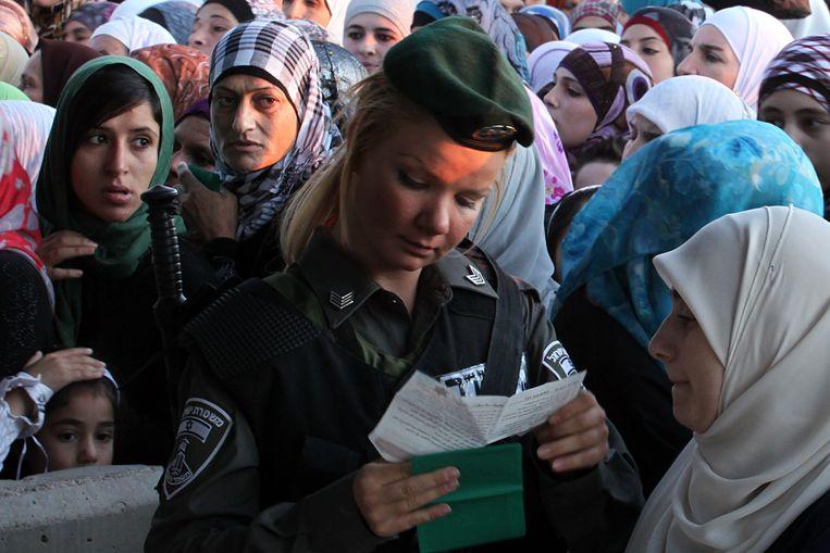 Palestijnse vrouwen op weg naar de Al-Aqsamoskee worden bij een grensovergang tussen de Westelijke Jordaanoever en Jeruzalem gecontroleerd door een Israëlische soldaat. Beeld Hollandse Hoogte / The New York Times Syndication