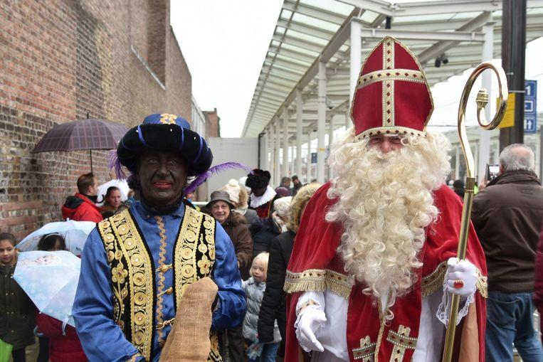 Een menigte kinderen en hun ouders verwelkomt Sinterklaas en Zwarte Piet in het station