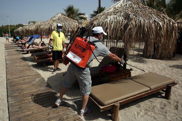 Een man desinfecteert een ligstoel op een strand bij Athene, Griekenland.