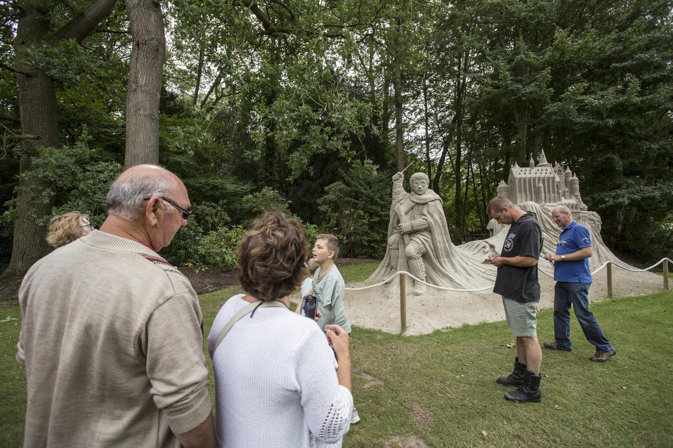 Publiek bij zandsculptuur van Harry Potter op Landgoed Warmelo in Diepenheim.