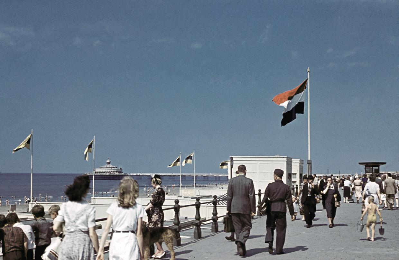 Een Duitse militair (met aktetas, midden) loopt tussen de badgasten bij de oude Pier van Scheveningen in juli 1941. De foto is gemaakt door Alphons Hustinx, een van de weinige fotografen die de oorlog op kleurenfilm vastlegde en van wie de foto's bewaard zijn gebleven. Beeld Hollandse Hoogte / Alphons Hustinx