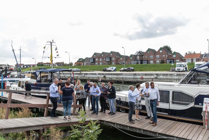 Bestuurders van de gemeente en de watersportvereniging proosten op de nieuwe passantensteiger in Tholen.
