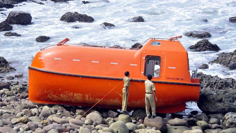 Indonesische ambtenaren onderzoeken een gestrande reddingsboot bij de kust van Java, op 25 februari 2014. De reddingsboot vervoerde 26 asielzoekers uit Pakistan, Iran en Afghanistan. Lokale media berichtten dat wordt vermoed dat ze met reddingsboot van de Australische autoriteiten kregen en zo werden teruggestuurd. Beeld anp