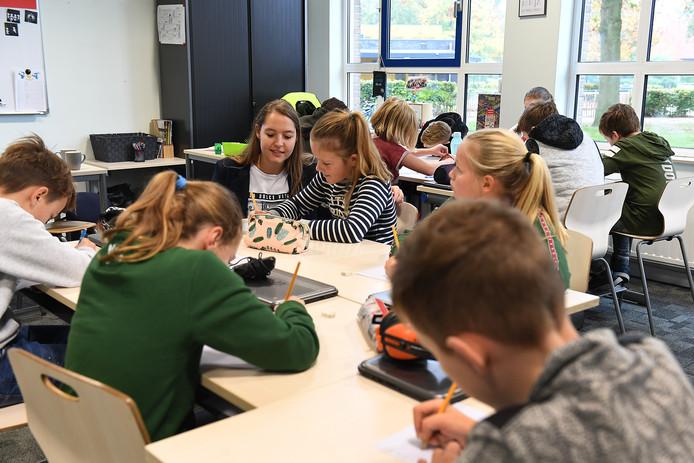 Juf Erinn tussen de leerlingen die druk bezig zijn met het schrijven van de brief.