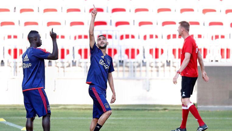 Ajacieden Sanchez (links) en Ziyech wijzen naar boven uit medeleven met Nouri tijdens de voorbereiding op de wedstrijd tegen OGC Nice. Beeld anp