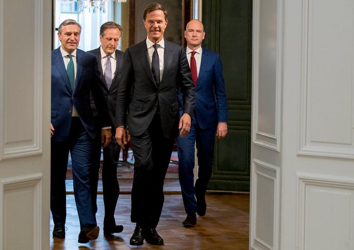 De onderhandelaars Sybrand Buma (CDA, links), Gert-Jan Segers (ChristenUnie, rechts), Mark Rutte (VVD, midden-rechts) en Alexander Pechtold (D66) voor de presentatie van het regeerakkoord.