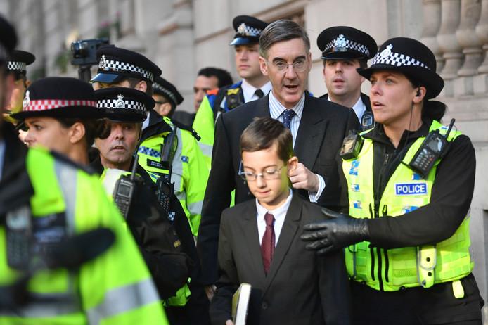De door demonstranten uitgescholden Jacob Rees-Mogg en zoon verlaten onder politiebegeleiding het Lagerhuis.