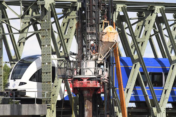 Bouwvakkers storten beton voor de nieuwe fietsbrug tussen Cuijk en Mook.