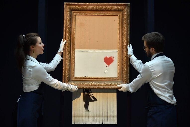 Medewerkers van veilinghuis Sotheby's met het kunstwerk in kwestie. Beeld AFP