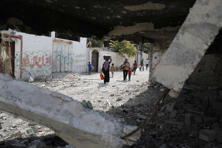 Een Palestijnse familie draagt bezittingen weg uit een verwoest huis in Beit Hanoun, dichtbij de grens met Israël. Beeld reuters