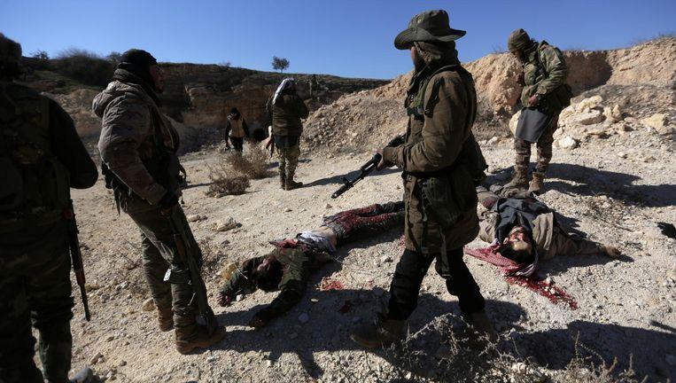 Door Turkije gesteunde rebellen staan in het noorden van Al-Bab bij de lichamen van strijders die volgens hen tot Islamitische Staat behoorden Beeld reuters