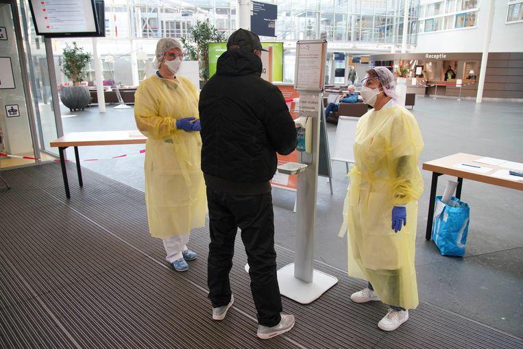 Bezoekers worden  bij ingang van het Flevoziekenhuis opgevangen en verzocht om hun handen te wassen.  Beeld BSR Agency