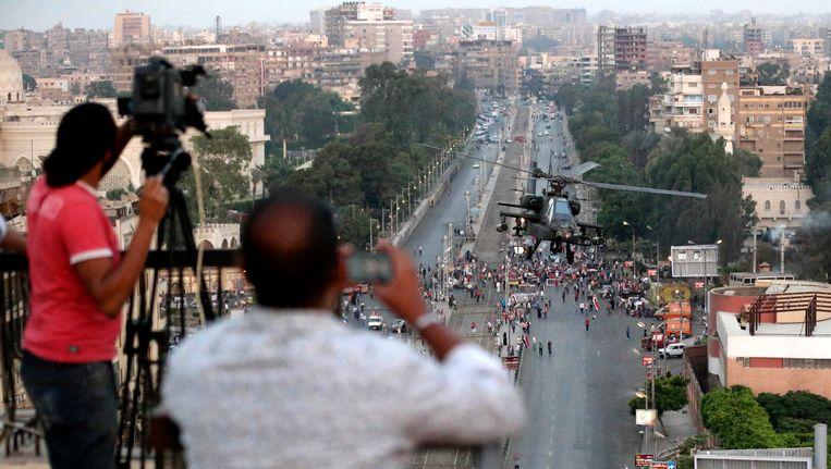 Journalisten op een dak in Caïro filmen een helikopteraanval. Beeld null