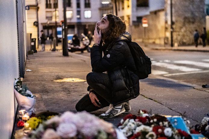 Parijzenaren bezoeken de herdenkingsplek van de aanslag op Charlie Hebdo voor het voormalige hoofdkantoor.