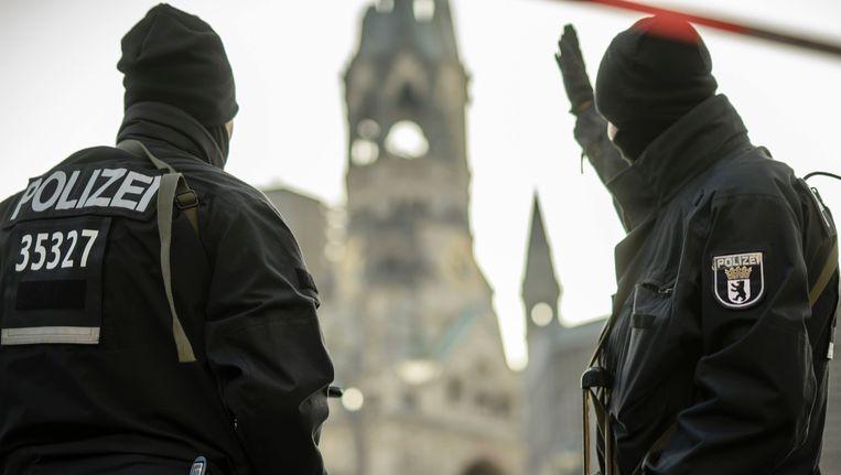 Twee agenten houden de wacht bij de Gedächtniskirche in Berlijn, waar maandagavond een vrachtwagen op een kerstmarkt inreed. Beeld AFP