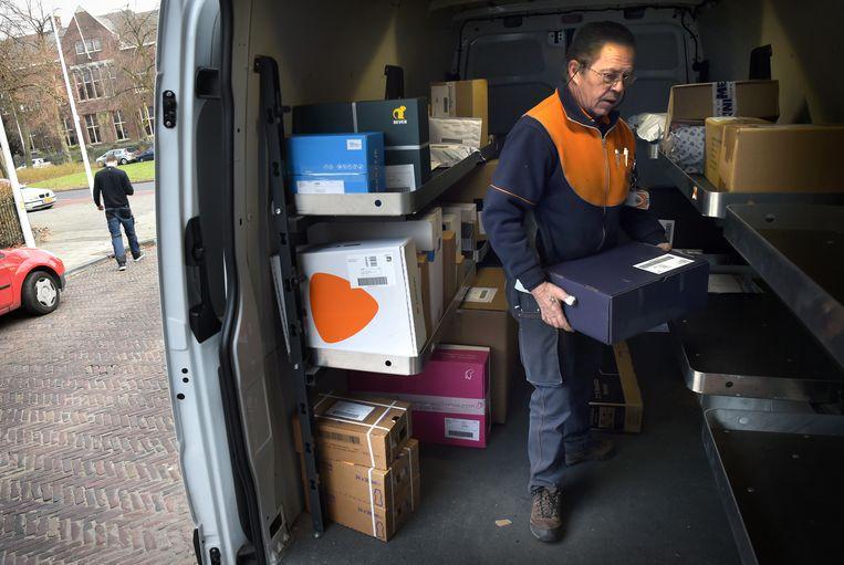 Een pakketbezorger van PostNL zoekt naar het juiste postpakket. Beeld Marcel van den Bergh