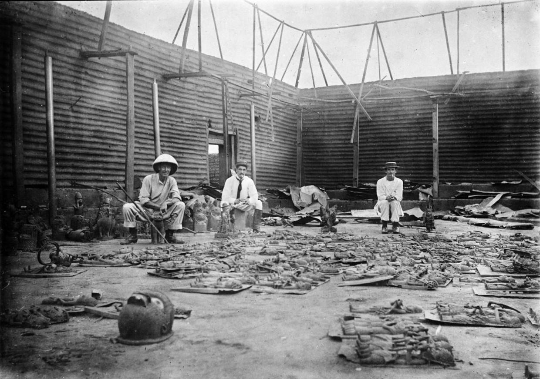 1897: leden van de Britse strafexpeditie poseren te midden van bronzen werken in het afgebrande paleis van de oba (koning) van het Beninrijk. De bronzen reliëfs, koningskoppen en andere objecten werden over de hele wereld verscheept