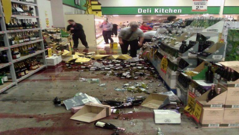 Medewerkers van een supermarkt ruimen de ravage op na de krachtige bevingen. Beeld REUTERS