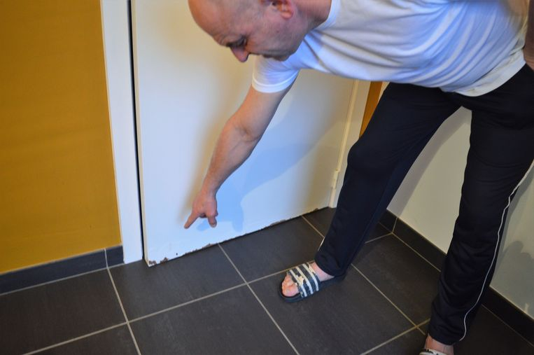 Luc toont de waterschade aan de deuren.