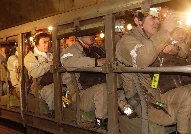 Japanse mijnwerkers dalen af naar een diepte van 600 meter om steenkool te winnen in een mijn bij Kushiro op het noordelijke eiland Hokkaido, in 2002. Inmiddels zijn alle Japanse steenkoolmijnen gesloten wegens de hoge productiekosten.  Beeld AP