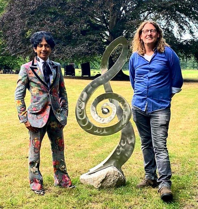 Pianist Wibi Soerjadi en kunstenaar Herman Wansing uit Neede bij een kunstwerk van de Needenaar in de tuin van de muzikant in Diepenheim.