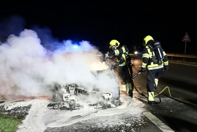 De brandweer blust de autobrand op de N323 bij de Prins Willem-Alexanderbrug tussen Echteld en Beneden-Leeuwen.
