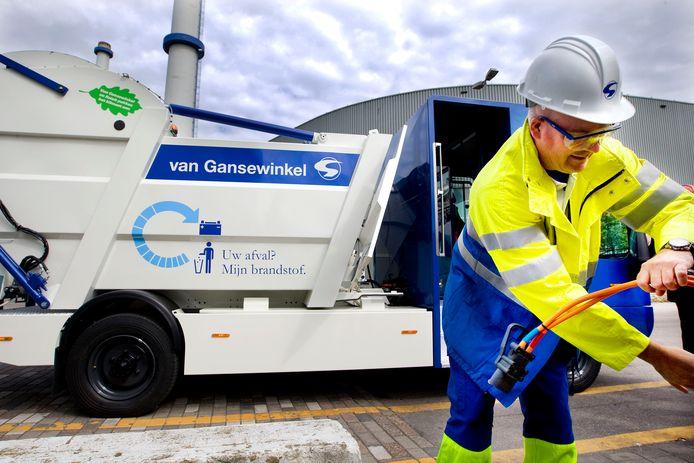 ROTTERDAM - Een vuilnisman demonstreert hoe het opladen werkt van de elektrische afvalwagen werkt. ANP ROBIN UTRECHT