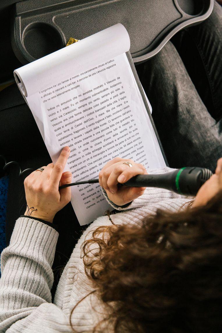 De gids van een literaire bustour leest voor uit werk van Elena Ferrante.  Beeld Gianni Cipriano