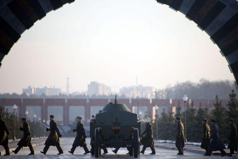Russische militairen lopen langs een wapentuig dat is uitgestald voor de begravenis van Michail Kalasjnikov. Beeld AFP