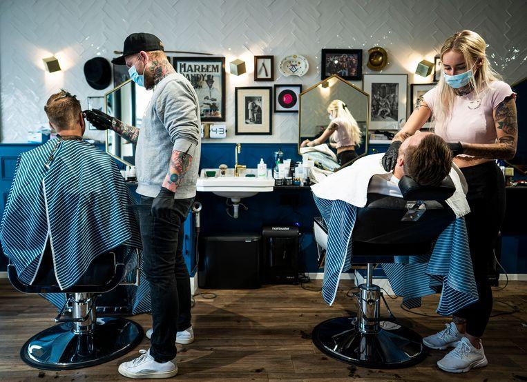 Klanten in de stoel bij kapper Amsterdam Dandy in Haarlem. Beeld Freek van den Bergh / de Volkskrant