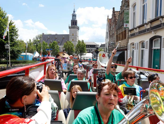 Feestkapel De Blaasknarren uit Leidschendam (groene shirts)verlaten de Markt in de dweilbus en gaan op weg naar hun optreden in OUd Hulst net buiten de binnenstad.