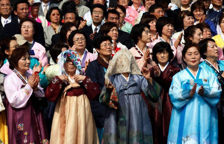 Noord-Koreaanse vrouwen wonen een militaire parade bij in 2012. Sommigen beschermen zich tegen de zon met een zakdoek over hun hoofd.
