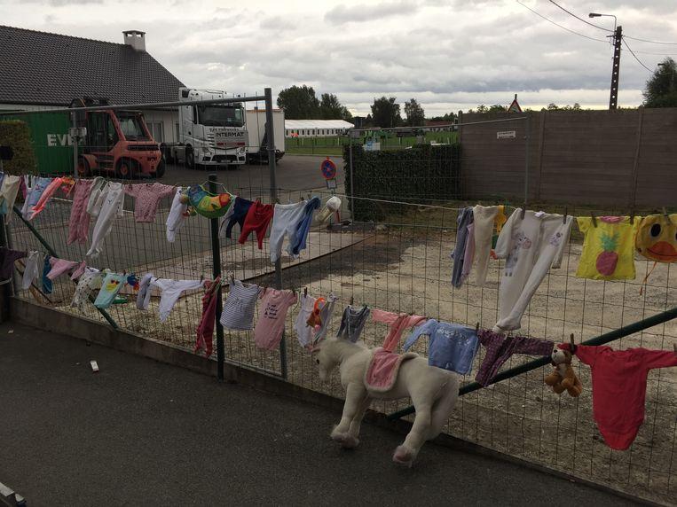De buren hebben de afsluiting van hun huis versierd met babyspullen