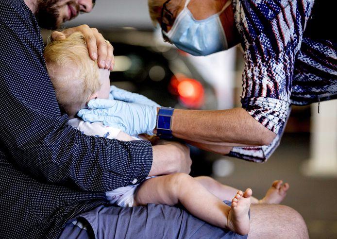 Een kindje wordt in een teststraat getest op het coronavirus.