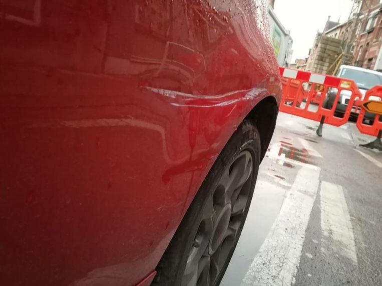 De wagen vertoont diepe krassen en ook de zijspiegel hangt los.